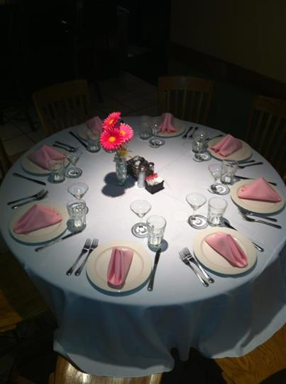 Big round table set with table sets and decorated with ink napkins and flowers