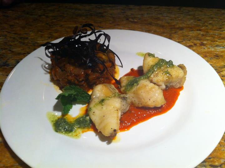 Monk fish special. We begin with Monk fish sautéed and plates over a red pepper sauce and topped with a basil pesto served with a side of sweet eggplant camponata.
