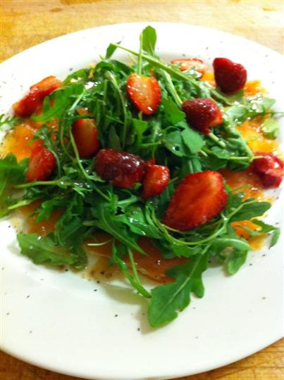 Green salad served with strawberries and dressing