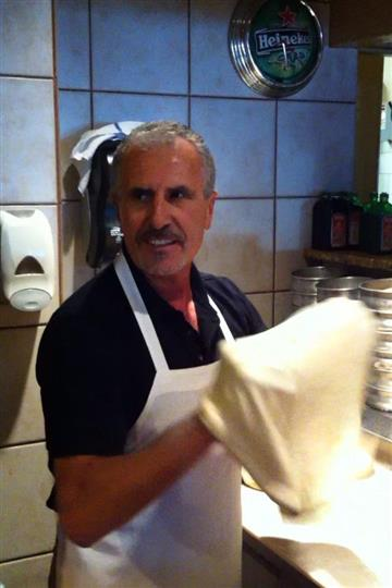 Man dressed in apron tossing dough for pizza