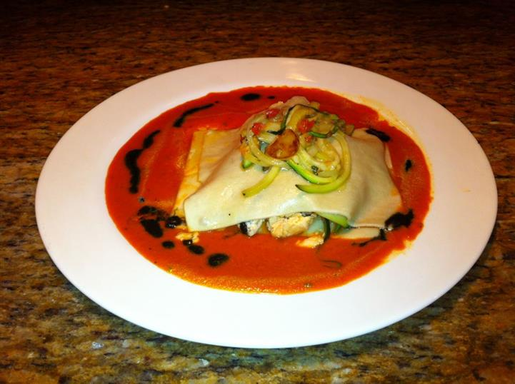 Lasagna dish with vegetables on top for garnish smothered in red sauce