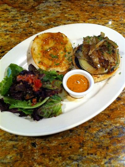 Open face bun topped with vegetables and drizzled with sauce served with green salad and sauce on the side