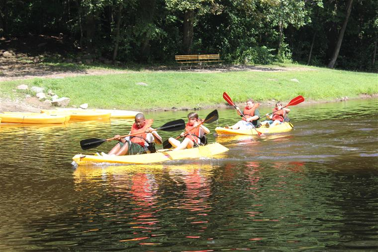 four children in kayaks in a lake