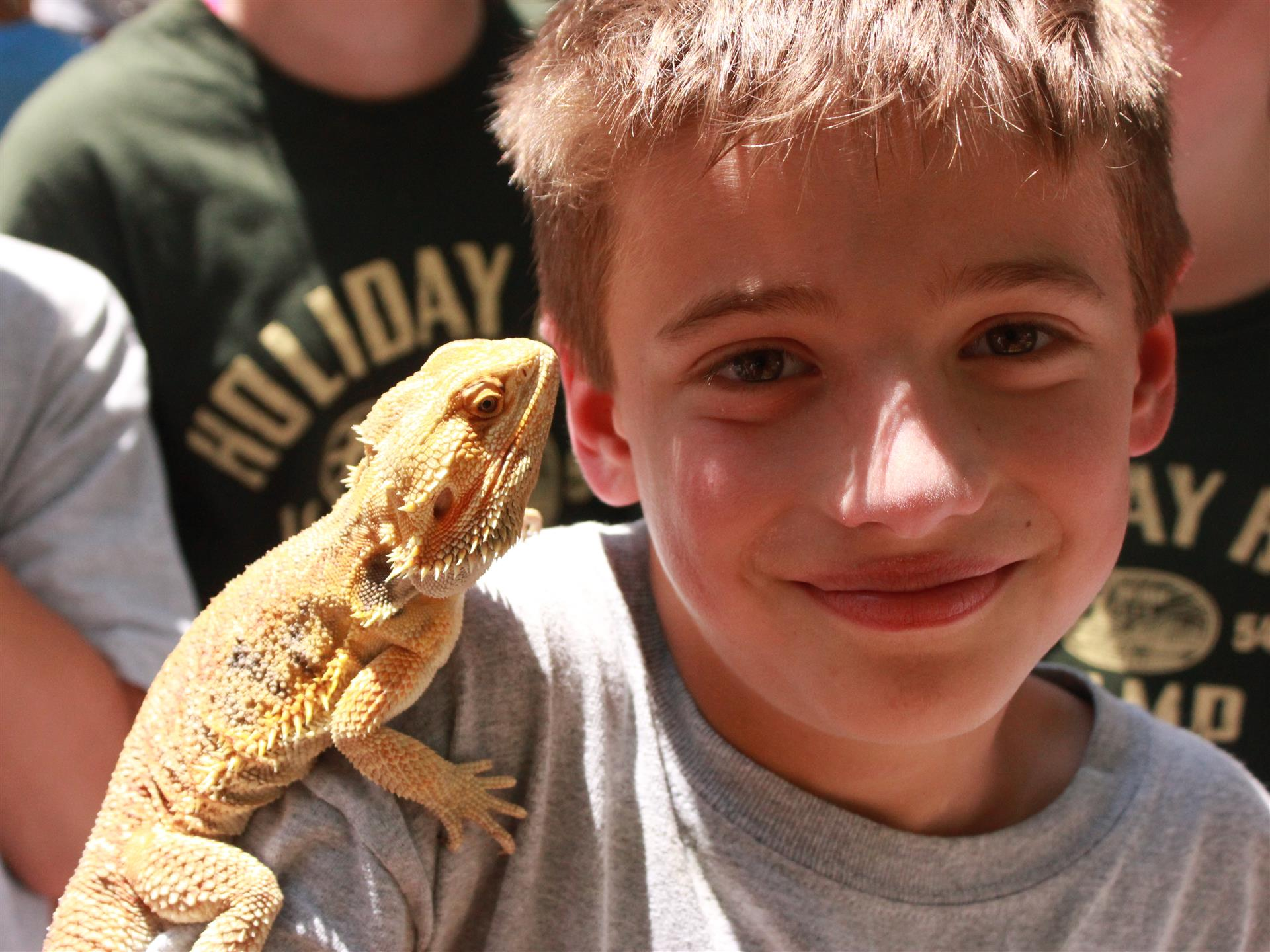 young boy smiling with iguana on his shoulder