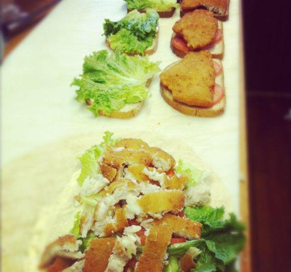 Chicken, lettuce, and tomato sandwiches being prepared