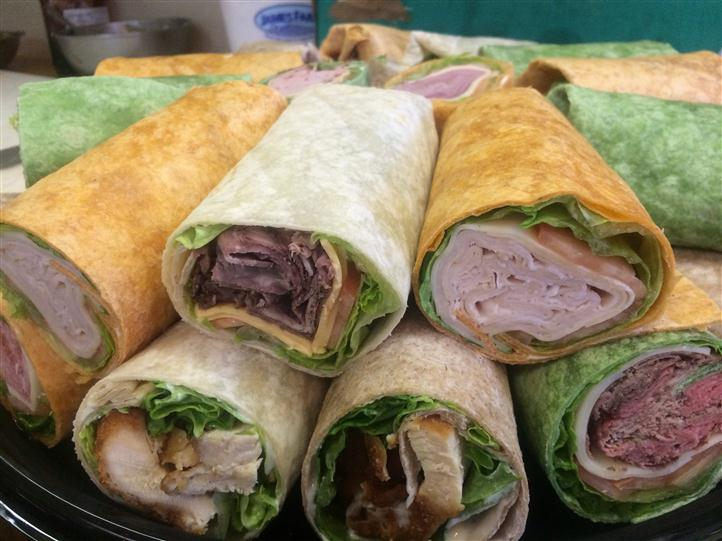 Up close photo of chicken and ham wraps stacked on top of each other