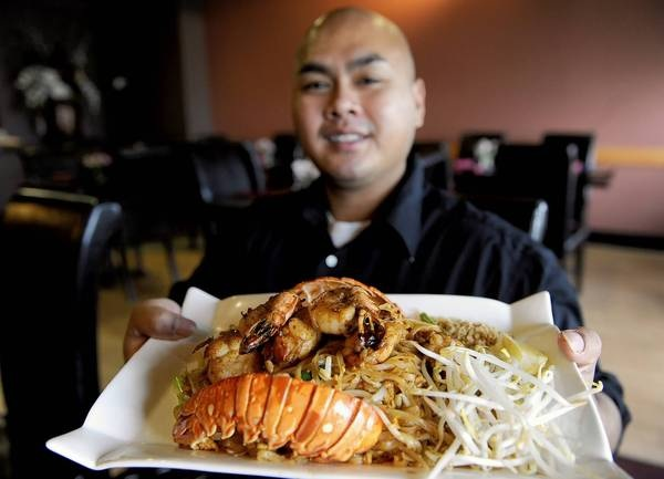 Restaurant owner holding a plate of food containing seafood, bean sprouts and fried rice