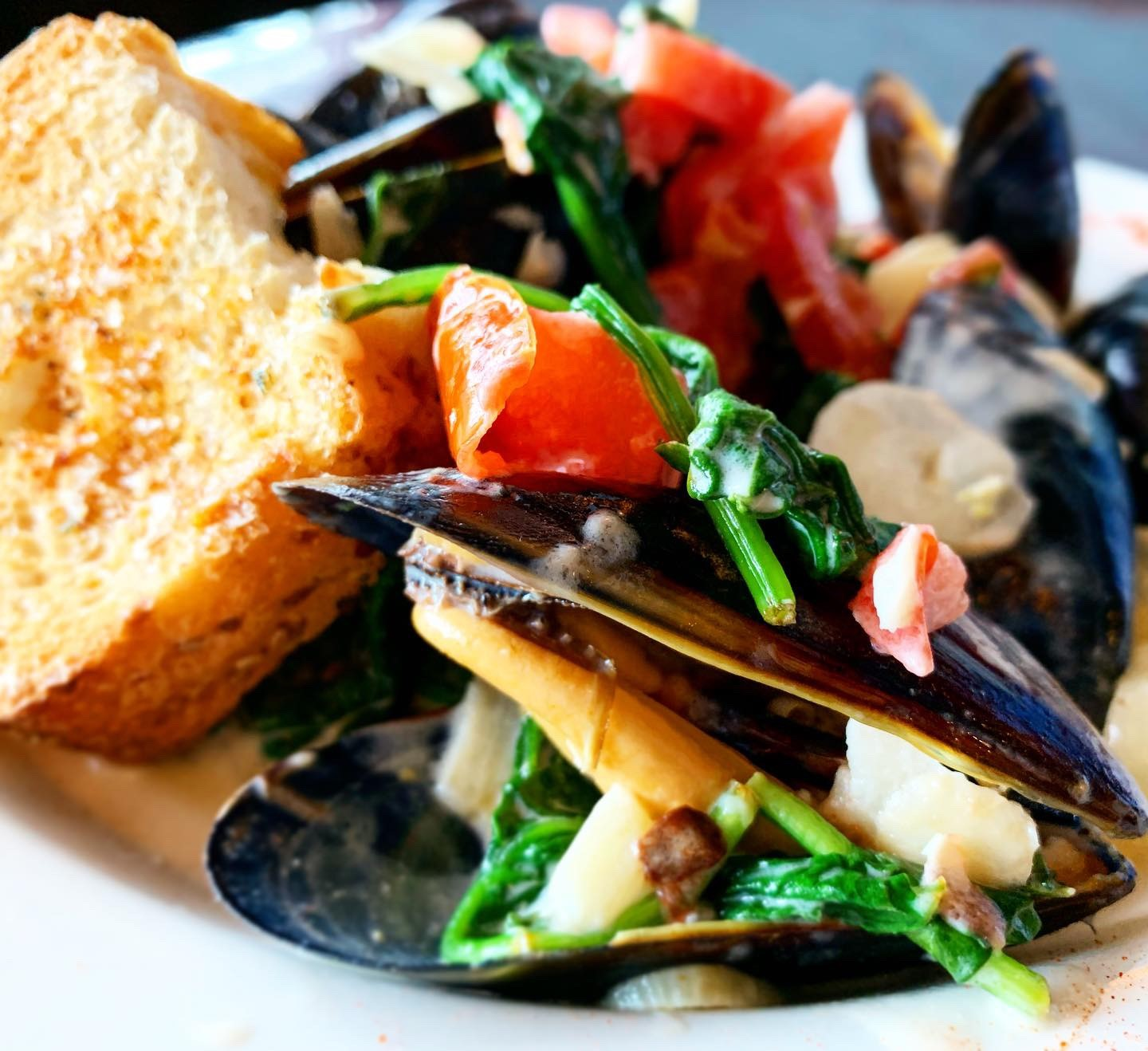 mussels in a white wine sauce with garlic bread on the side.