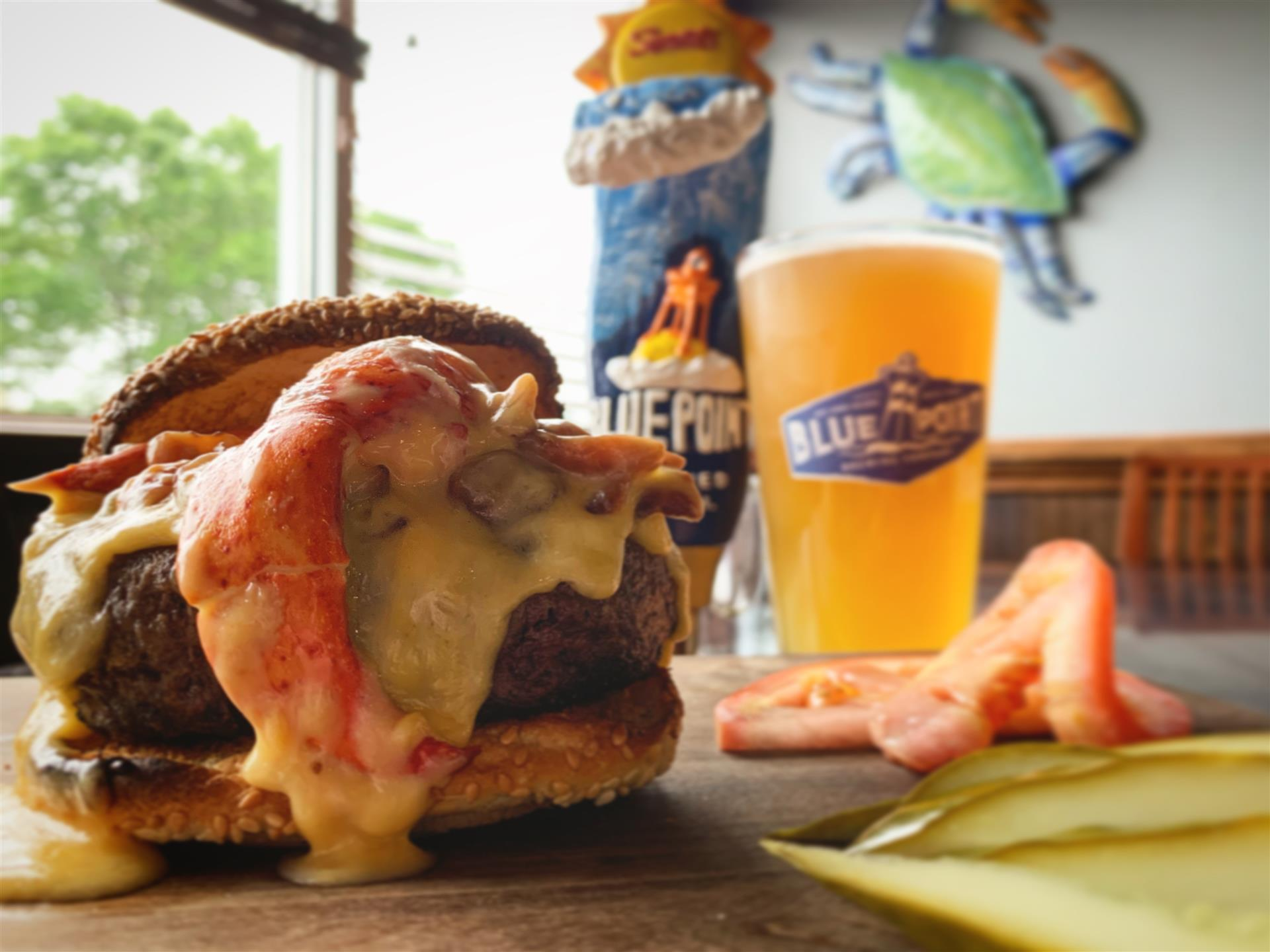 burger topped with lobster and melted cheese. pint of a summer ale on the side.