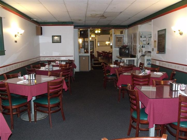 Dining hall with wooden tables and chairs covered with dark red linen