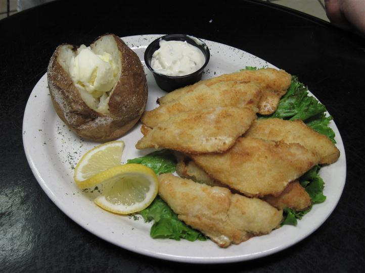 Baked potato with fried fish and a peeled lemon