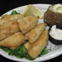 Fried fish with baked potato and lemon slice