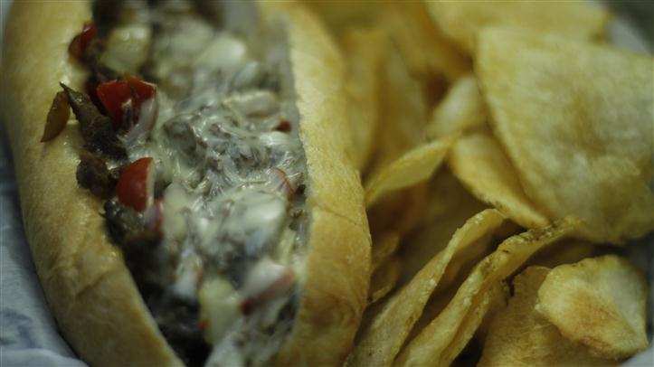 Philly cheesesteak sandwich with a side of potato chips