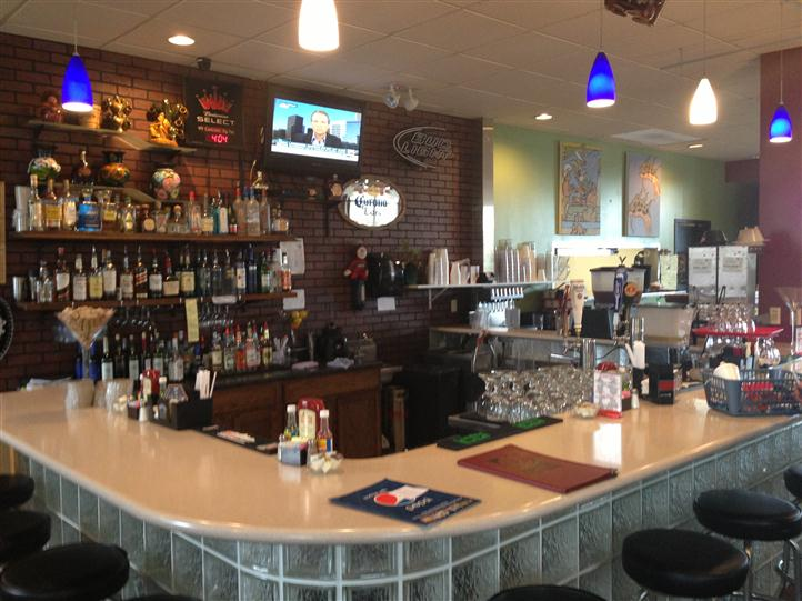 bar area displaying a wall of liquor bottles on shelves, counter, tv and stools