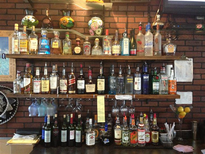 bar area displaying a wall of liquor bottles on shelves