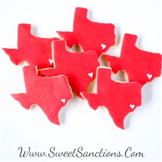 Cookies shaped like the state of texas with red frosting