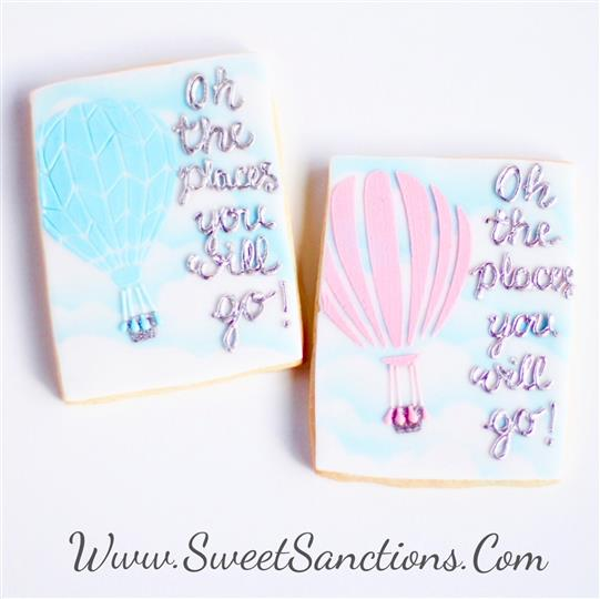 "2 cookies with ""oh the places youll go"" written in frosting"