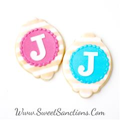 "two striped cookies with the letter ""J"" on each"