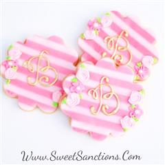 "3 striped cookies with the initial ""B"" frosted on top"