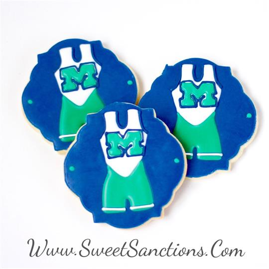 three cookies with wrestling uniforms on them