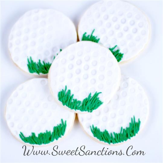 5 cookies designed as golf balls with grass on them