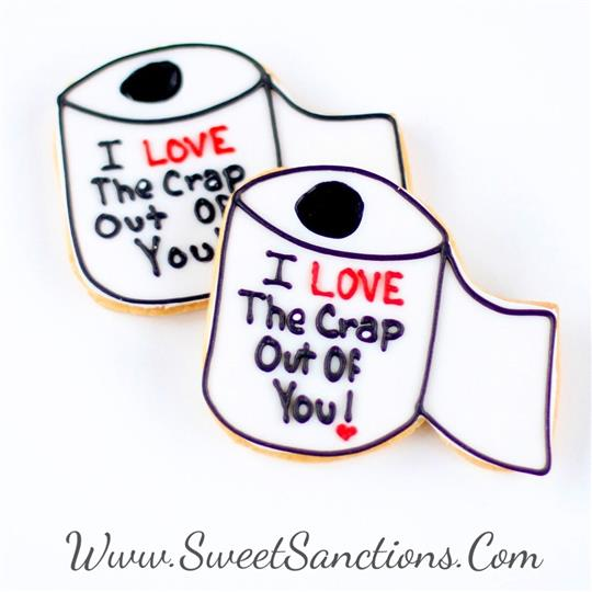"two cookies shaped as toilet paper rolls with ""i love the crap out of you!"" written in frosting on top."