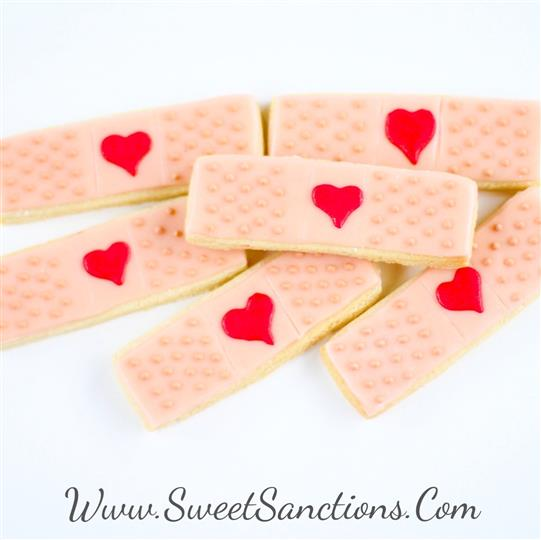 6 cookies shaped as bandaids with hearts painted on top