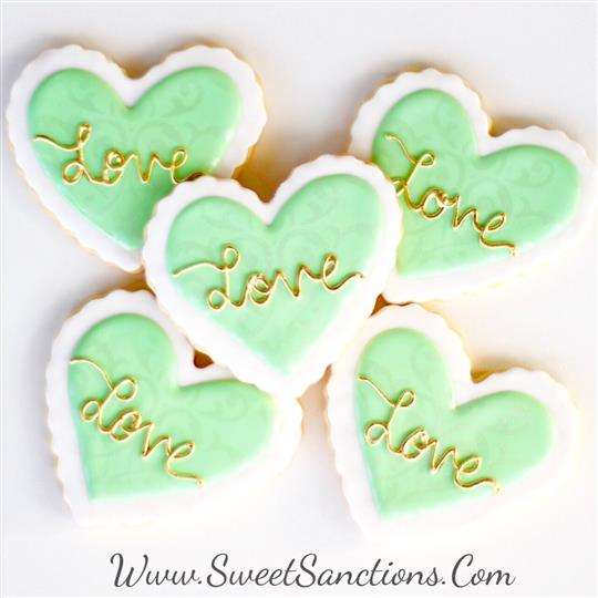 "5 cookies shaped as hearts with a frosting trim and ""Love"" written in frosting on top"