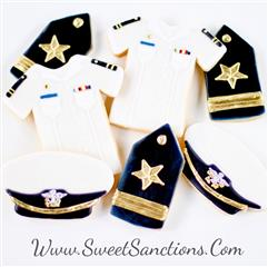 two cookies shaped and painted as navy shirts, three cookies shaped and painted as navy badges, and two cookies shaped and painted as navy hats