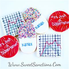 "Two cookies in the shape of a cirlcle with ""it's just a dissertation"" written in frosting on top. 2 cookies with a graph decorated on top with frosting. 2 cookies decorated as pills with sprinkles and ""xanax"" writtin on top in frosting."