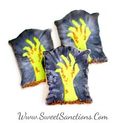 3 cookies shaped as tombstones with zombie hands painted on them