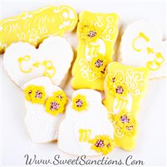 2 cookies shaped and decorated as wedding cakes with sunflowers on them, 3 cookies shaped and decorated as plaques with sunflowers on them, and two cookies shaped as hearts with frosted initials on top.