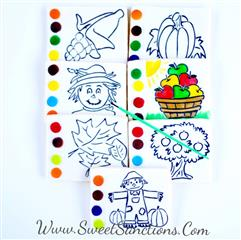 7 square cookies with outlines of a corn, a pumpkin, a scarecrow, a basket of apples, leaves, an apple tree, and a scarecrow with 2 pumpkins. 4 colors on each side to fill in the outlines.
