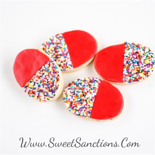 four oval shaped cookies with sprinkles on one side