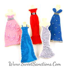 5 cookis shaped an painted as dresses. onne is pink with a silver belt, another is a blue with texture in frosting, another is slim and red with a black belt, once is silver with textured frosting, and another blue with silver frosting dots
