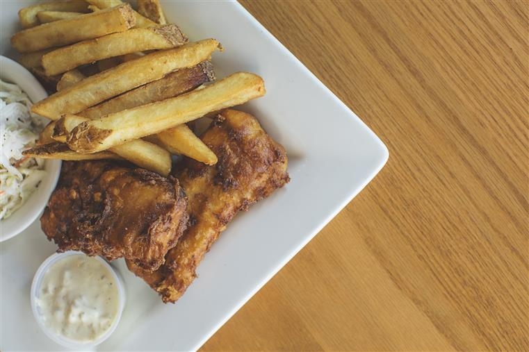 wings with dipping sauce, french fries, and coleslaw on a plate
