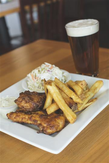 wings, fries, coleslaw on a plate with a beer