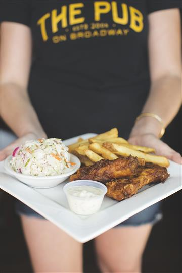 waitress holding plate of wings, fries and coleslaw