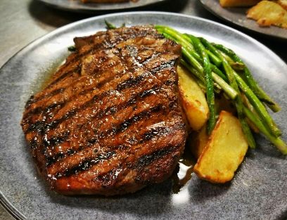 Grilled steak on a pan next to potato wedges and asparagus
