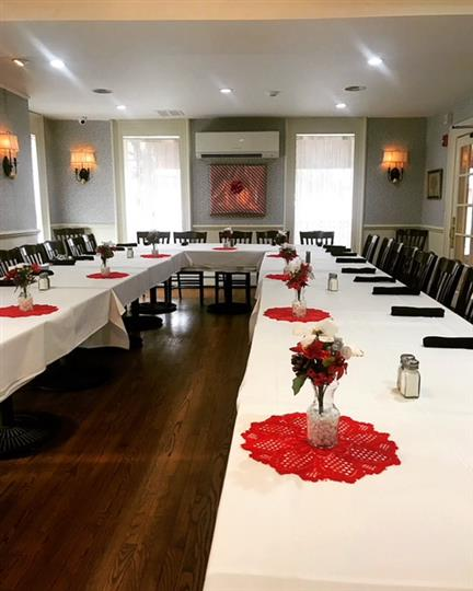 three long tables with white table clothes and black napkins with place settings and chairs for everyone