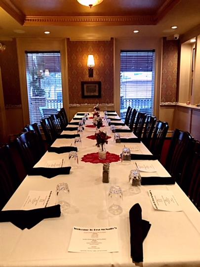 A long table with a white table cloth and black napkins with place settings and chairs for everyone