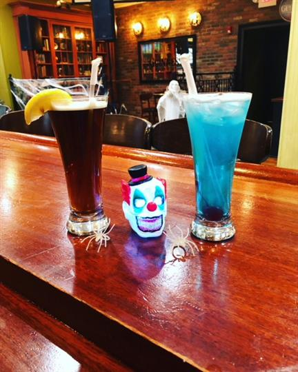 Two mixed drinks one colored brown like cola and the other blue with a clown head in between