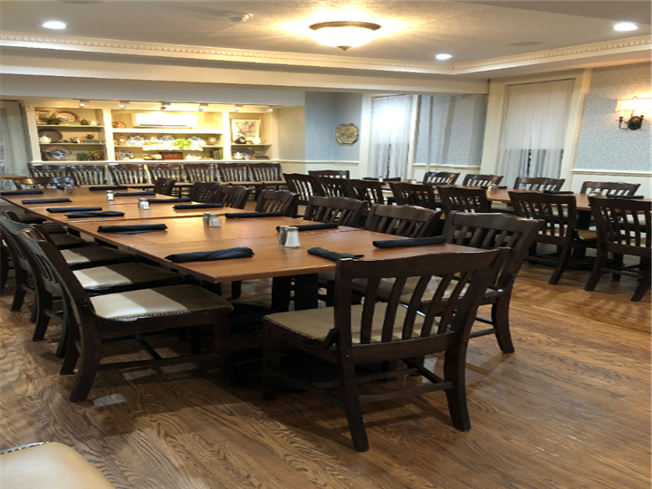 Multiple wooden tables with wooden chairs with a black napkin rolled with utensils