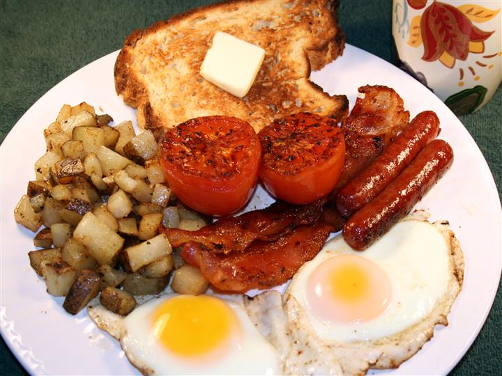a plate with two sunny side up eggs, two sausages, hash browns, two halves of a tomato and toast with butter