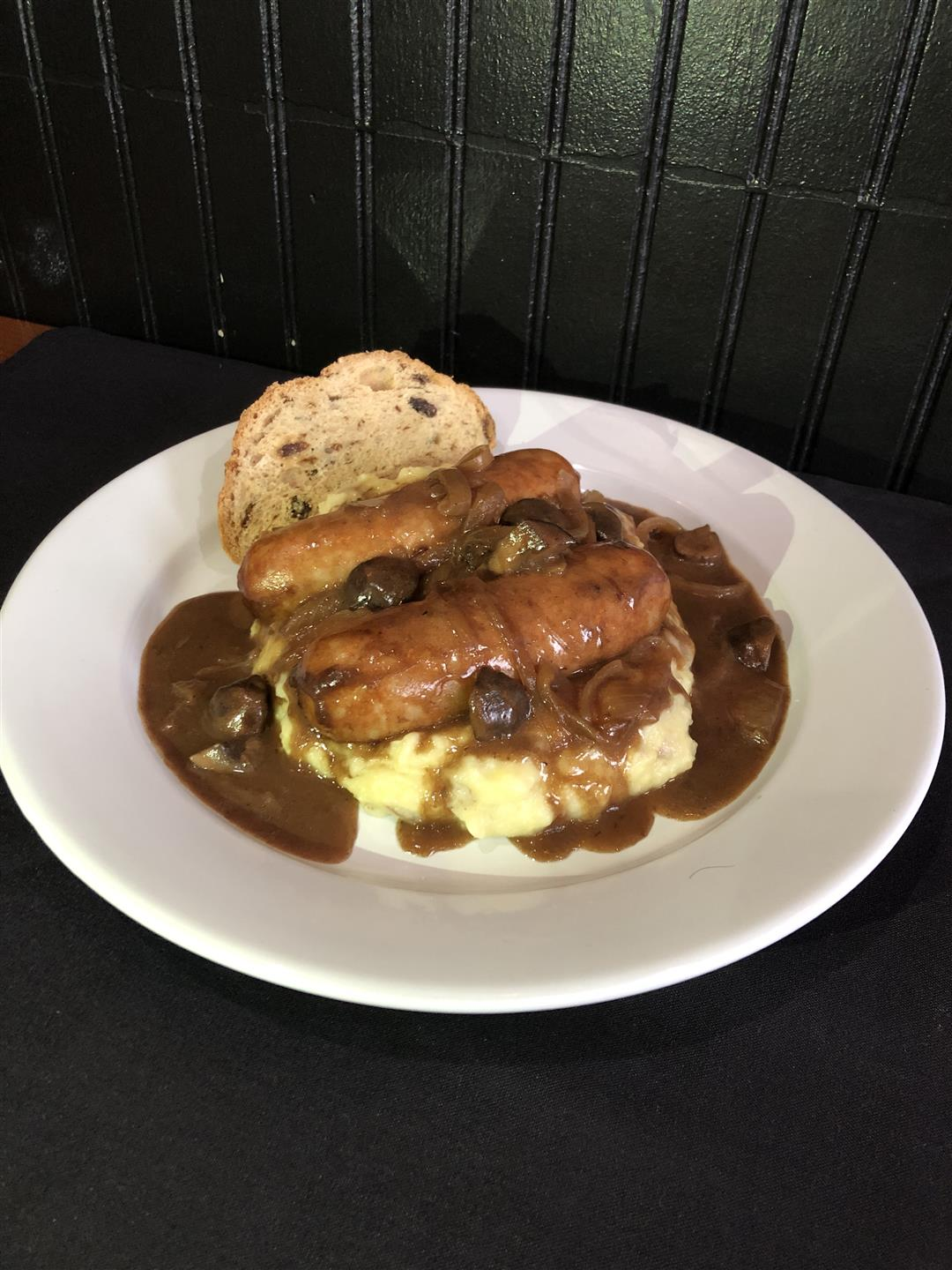 a plate of bangers and mash with irish soda bread