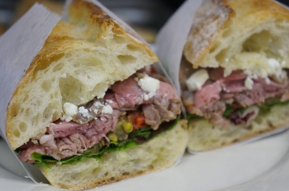 roast beef sandwich on a roll with spinach and feta cheese