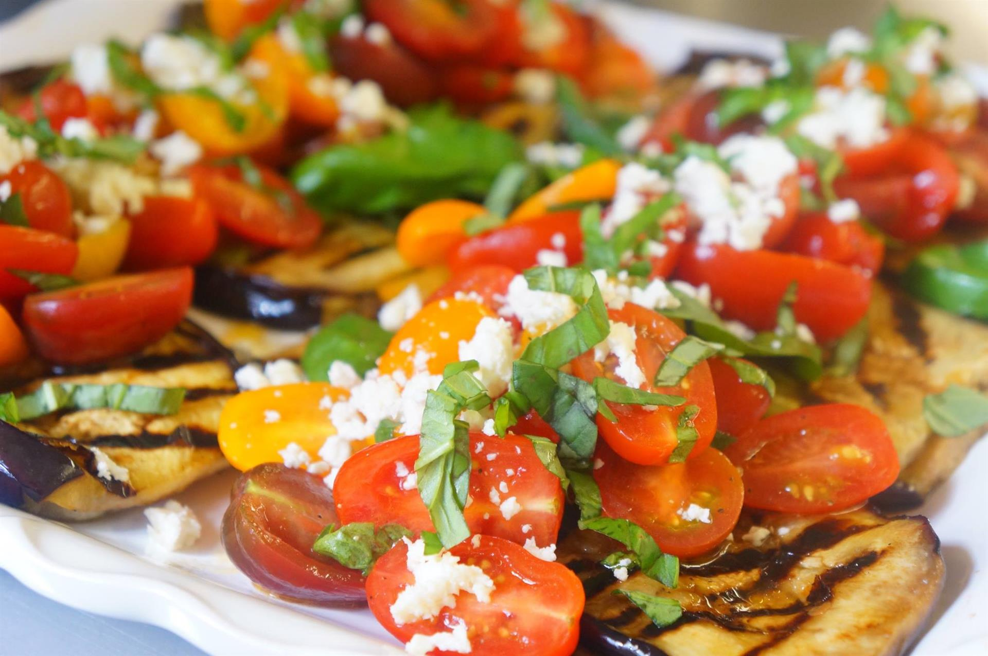 A Bruschetta platter with cherry tomatoes, parsley, and shredded white cheese, topped with vinaigrette sauce