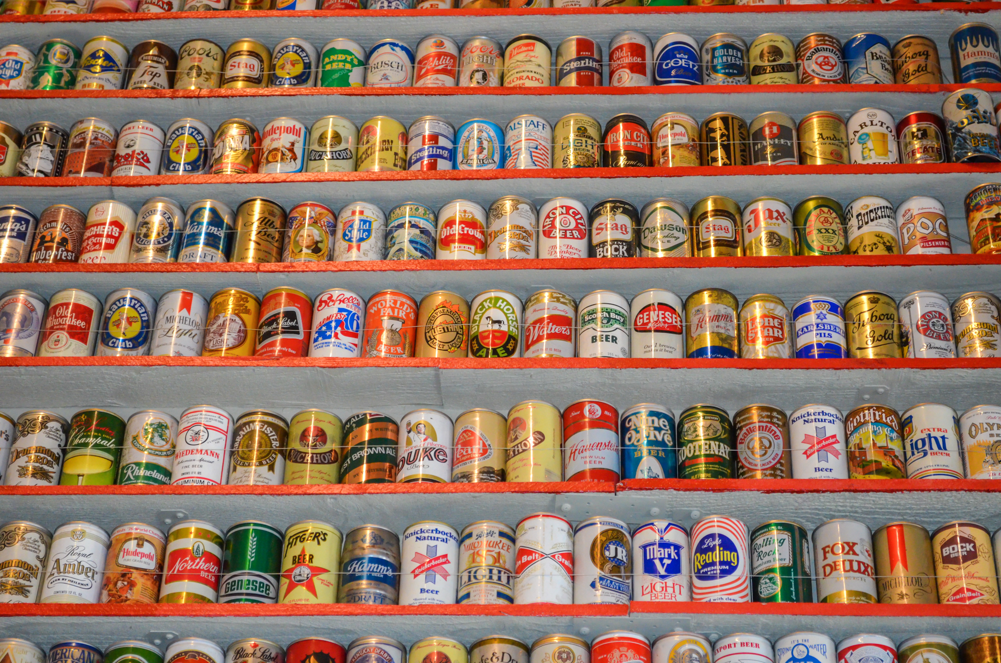 Closeup on an entire wall full of different beer cans.