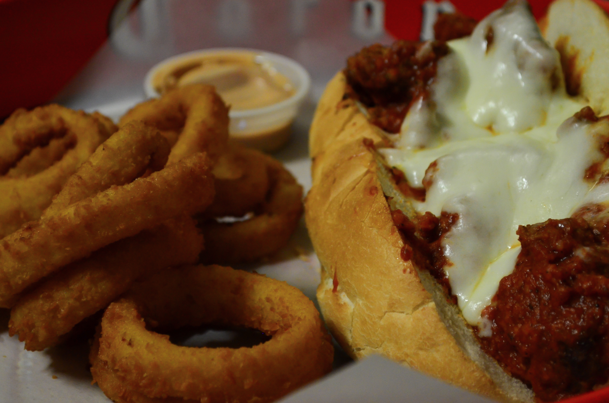 Meatball parmesan sub with a side of onion rings.