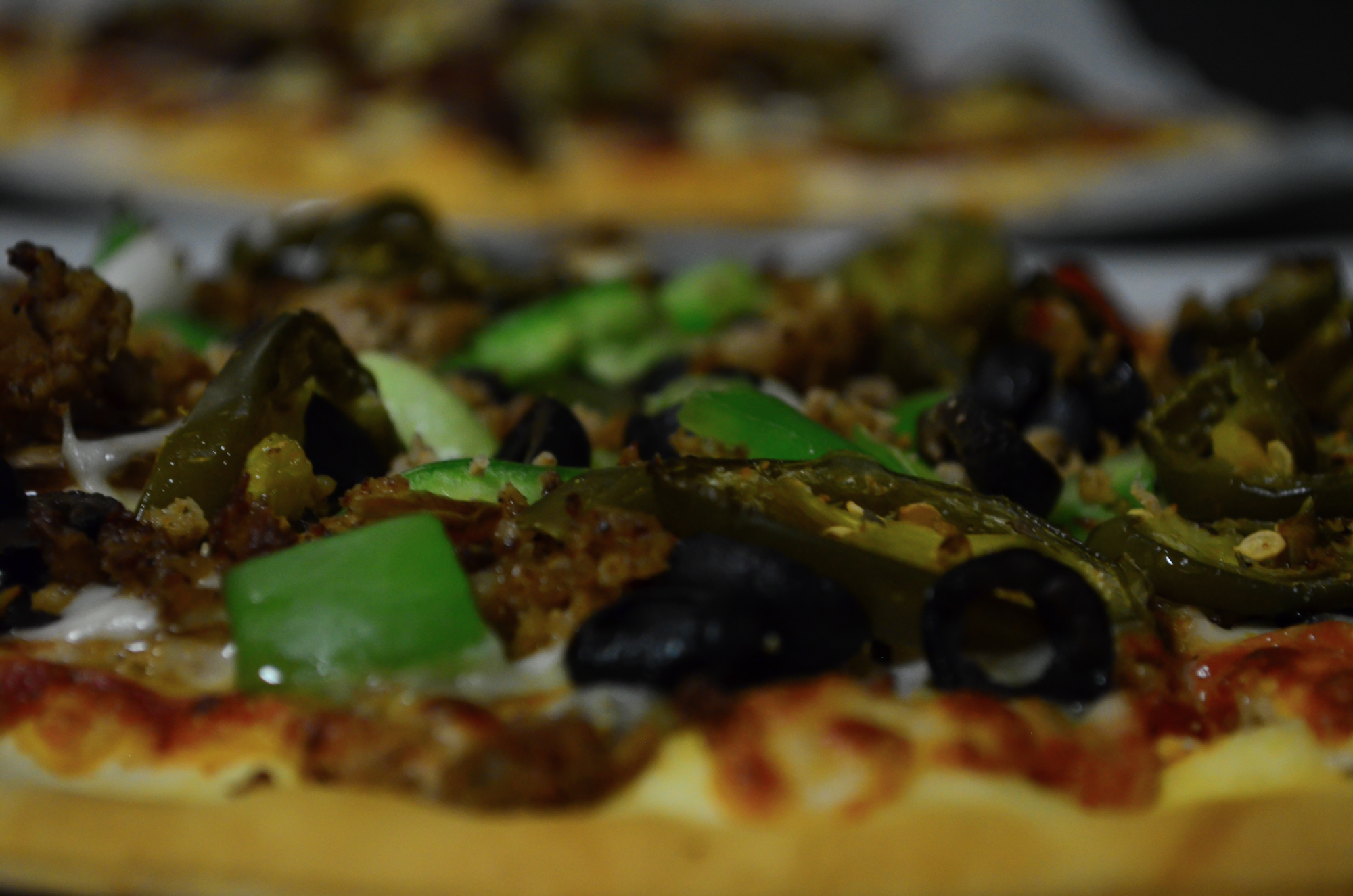 Closeup of pizza with olives, jalapenos and green peppers.